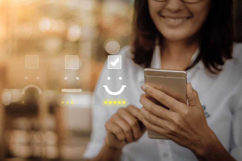 Businesswoman pressing face emoticon on virtual touch screen at smartphone