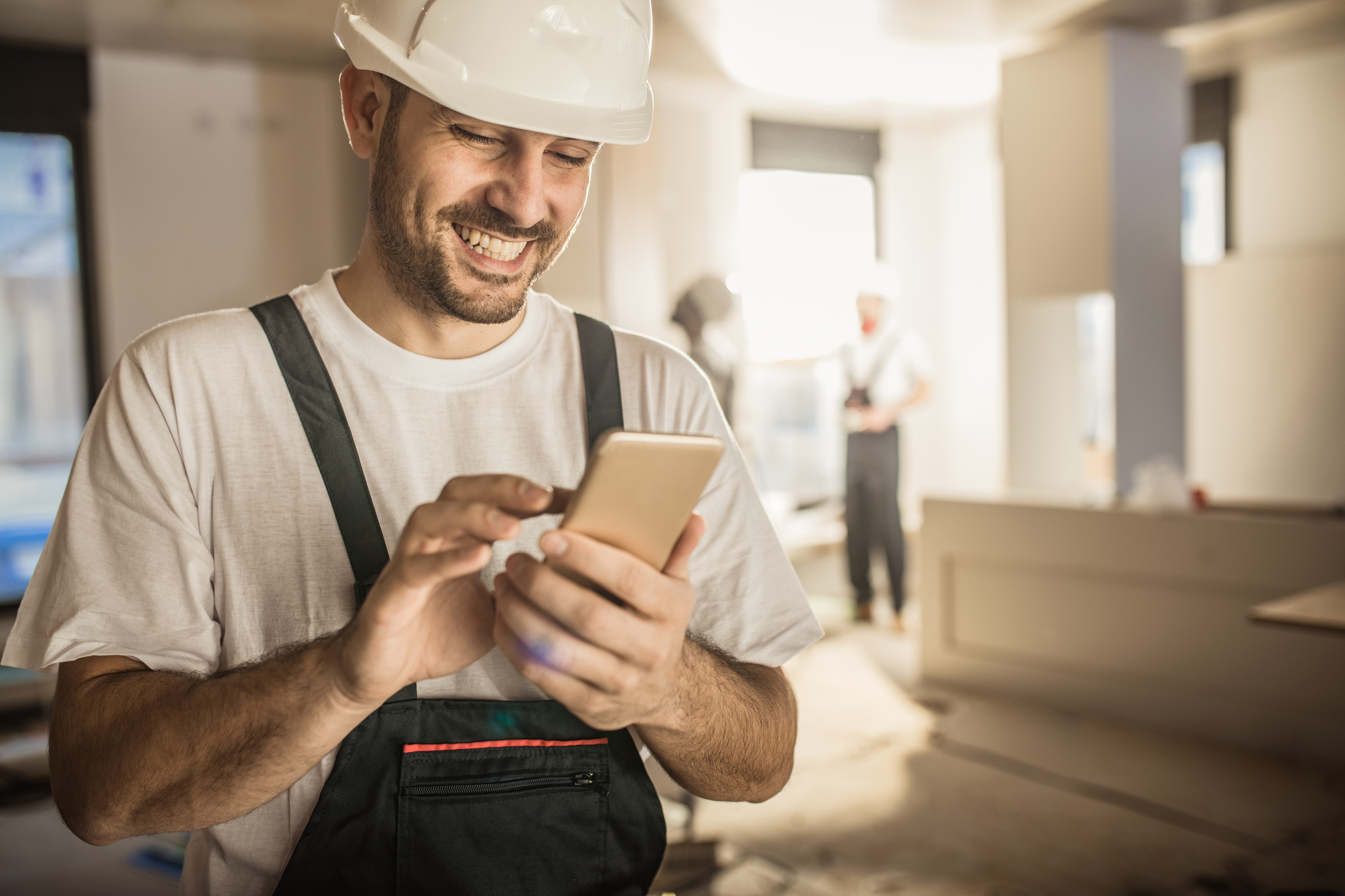 Happy male worker text messaging on smart phone while being in renovating home