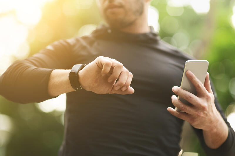 Man using wearable fitness tracker and smartphone