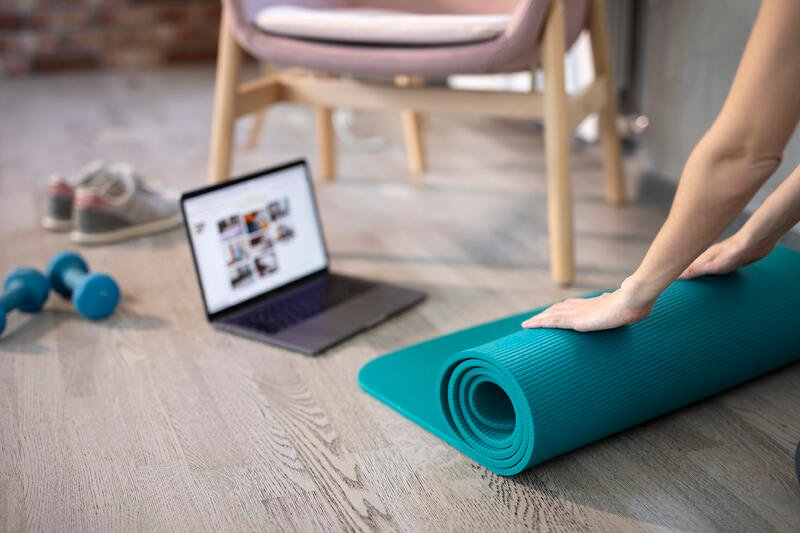 Person prepares for online activity with yoga mat