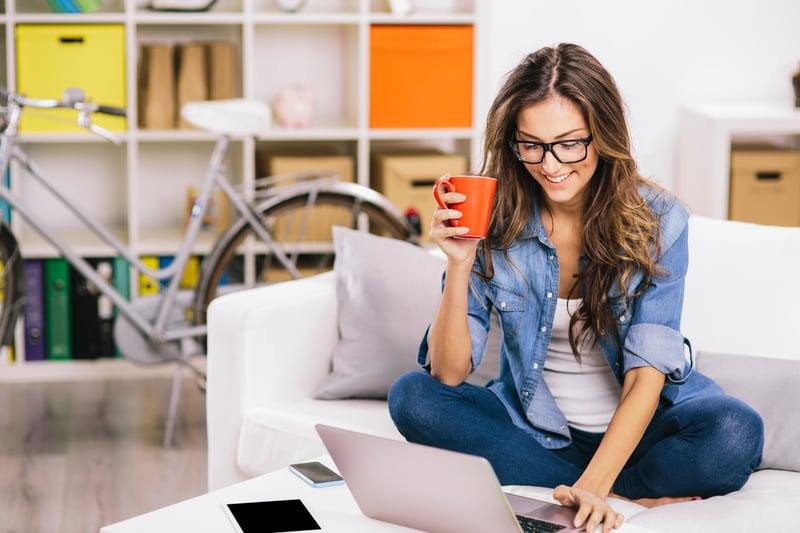 Woman sitting on sofa using a laptop