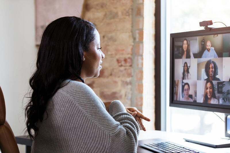adult woman uses video conferencing to meet with her colleagues