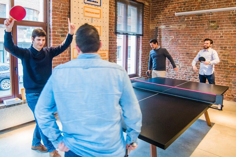 group of men playing table tennis at work