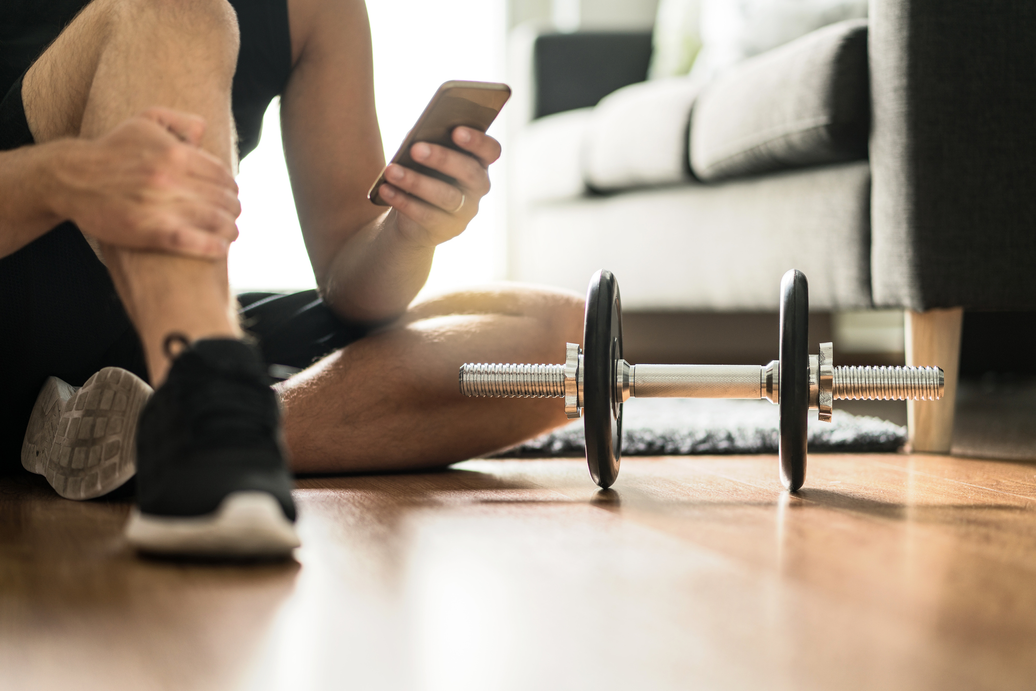 Man using smartphone during workout at home