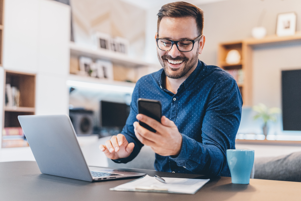 Smiling man looking a cell phone at home office