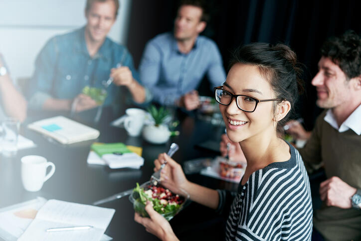 Co-workers around conference table eating salad
