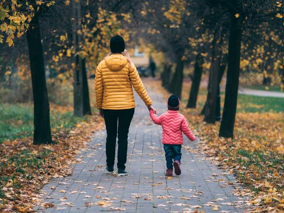Woman and child walking hand-in-hand in fall