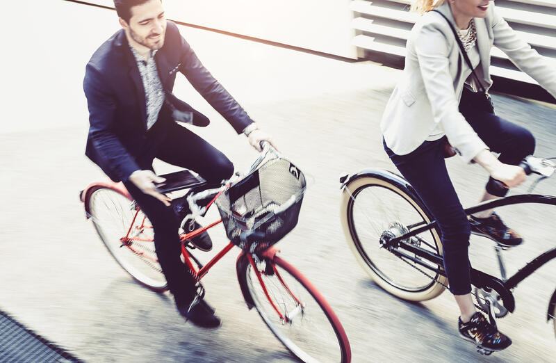 man and woman cycling in business attire