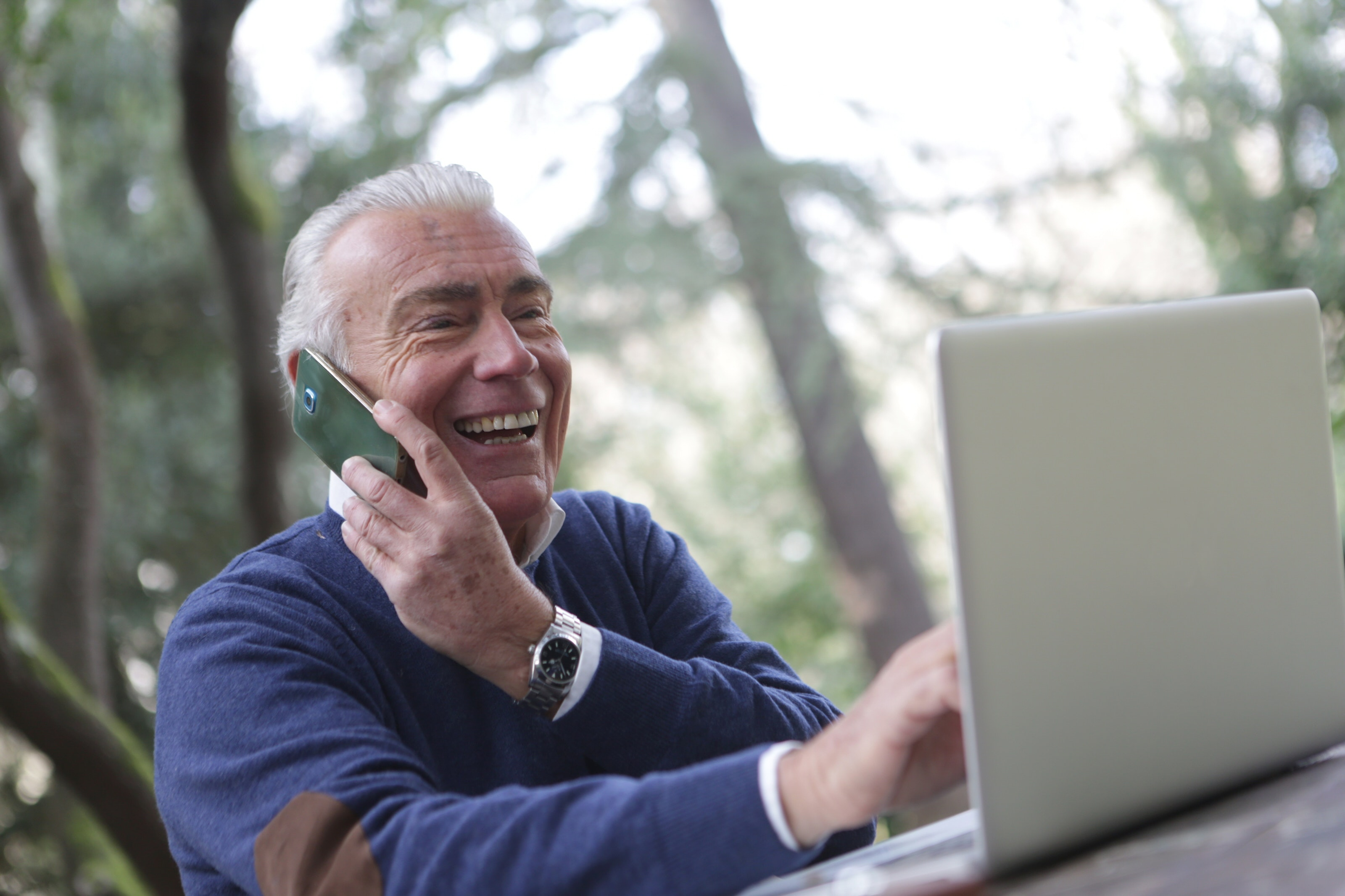 Older man outdoors on phone with laptop