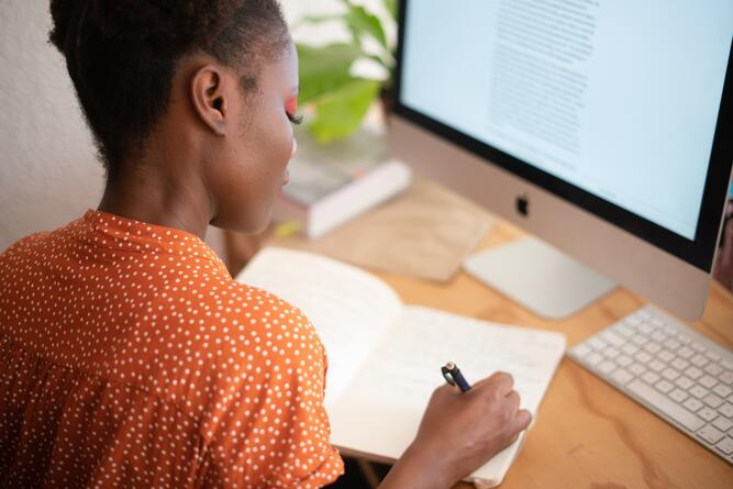 Woman at desk writing in notebook