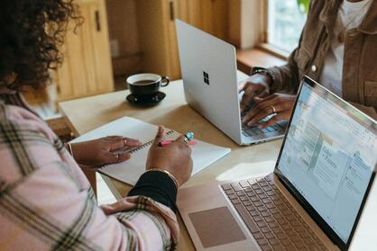 Two women working at laptops