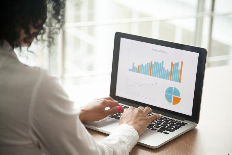 woman looking at graphs on laptop