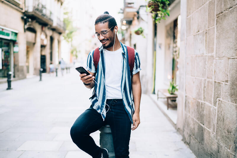 young black man smiling while using smartphone