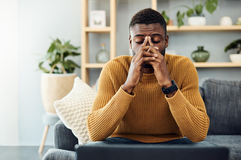 young black man stressed out sitting on couch