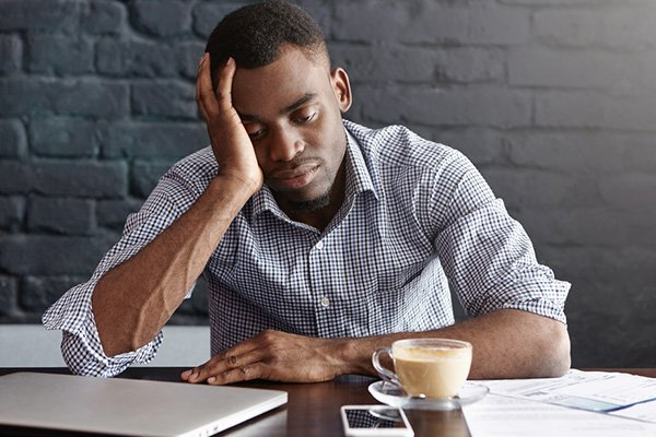 young black man stresses while working from home