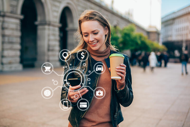 young woman using a smartphone with various icons of smart technology
