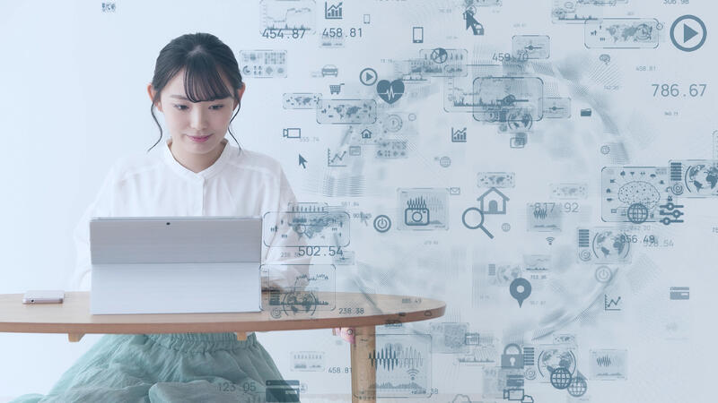 young woman using laptop with technology icons floating in foreground